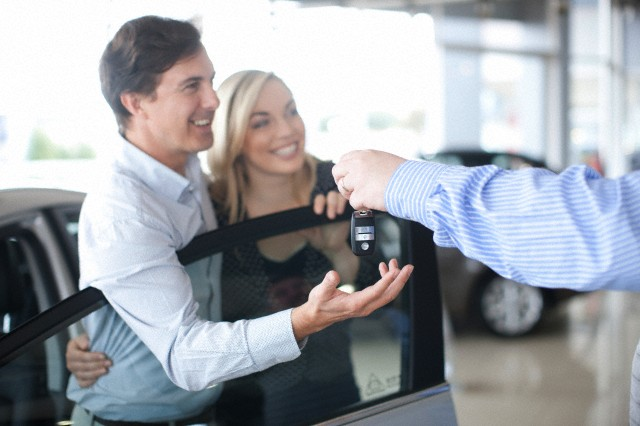 Car salesman handing key to couple in showroom --- Image by © Zero Creatives/Corbis