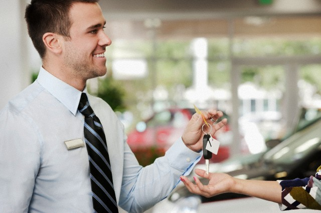 Irving, Texas, USA --- Man handing woman keys to new car in showroom --- Image by © DreamPictures/Blend Images/Corbis