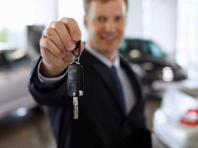 Salesman holding out car key in automobile showroom --- Image by © Ocean/Corbis